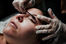Crop Anonymous Cosmetician In Latex Gloves Curling Eyelashes Of Female Patient During Lash Lift Procedure In Salon