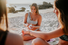 Happy Young Female Friends In Swimwear Having Fun And Playing Cards While Spending Summer Day Together On Sandy Beach
