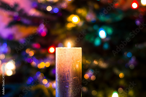 Obraz christmas festive concept with christmas tree and colorful lights and burning candle - fototapety do salonu