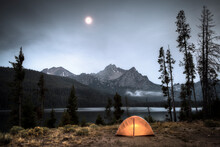Scenic View Of Moonlit Sky Over Tent Illuminated By Stanley Lake Against Sawtooth Range