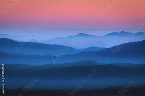 Scenic view of fog over mountains during sunrise