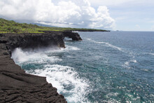 Volcanic Coastal Cliffs With Blue Waves Breaking During Sunny Day