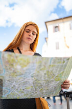 Red Hair Woman In A City Looking At Paper Map With Blue Sky Backgroung