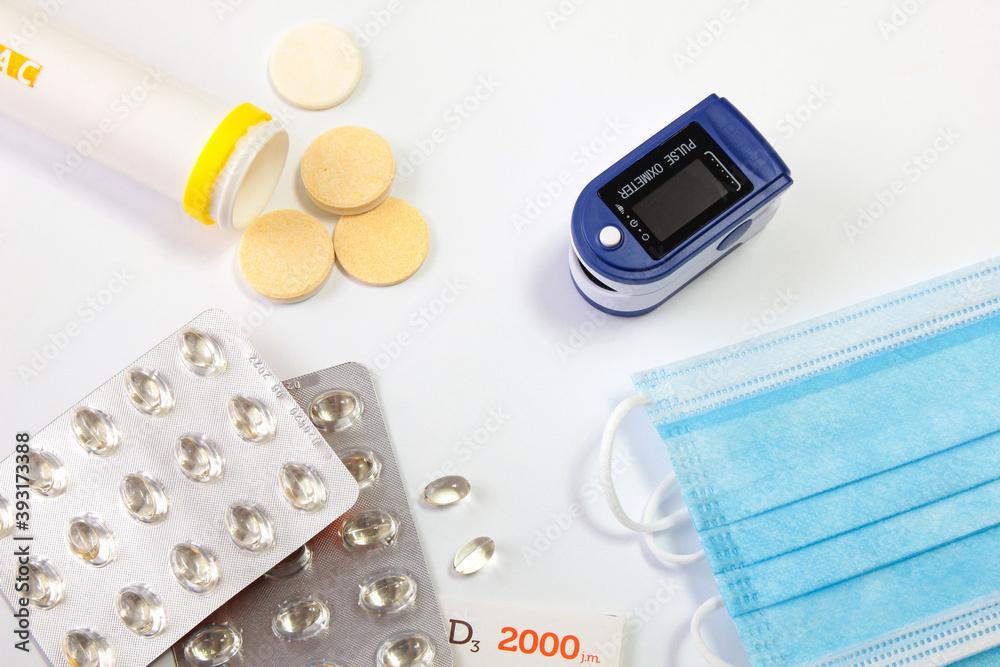 Fototapeta Witamina C i D, pulsoksymetr i maseczki jednorazowe. Środki wspomagające odporność i  leczenie koronawirusa