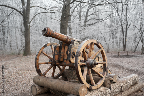 Fotografia Old wooden cannon of the Cossacks, on a pedestal in the winter forest