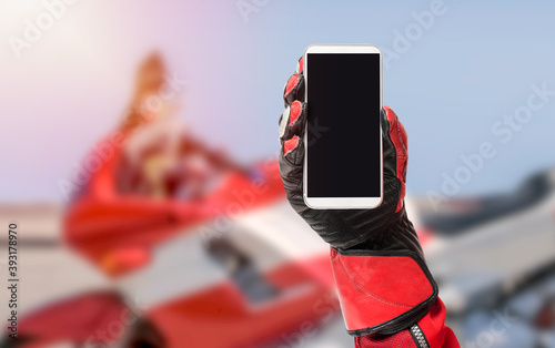 Fotografiet Biker hand holding smartphone with blank screen, cropped image, copy space, blan