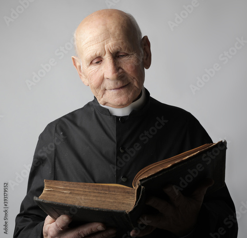 portrait of a old priest with bible Fototapeta