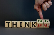 Think Small Or Think Big Concept. Hand Flips Cubes And Changes The Words 'think Small' To 'think Big' Or Vice Versa. Beautiful Grey Background. Business Concept. Copy Space.