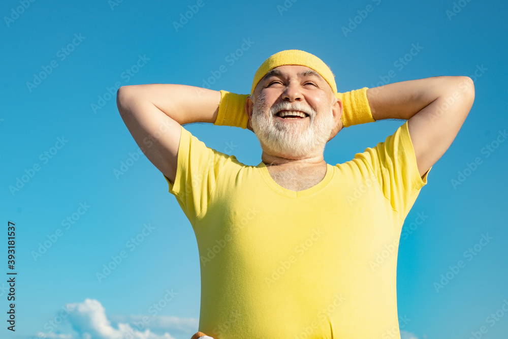 Fototapeta Freedom retirement concept. Elderly man practicing sports on blue sky background. Healthy and sport. Healthcare cheerful lifestyle.