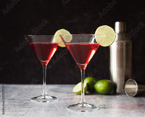 Cosmopolitan martini drinks, shaker and limes on a gray counter.