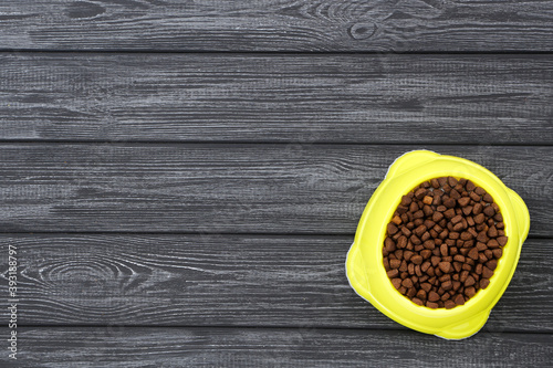 Dry pet food in bowl on black wooden table