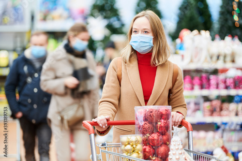 Fotografiet woman in mask buying new year decoration in shop at coronavirus lockdown