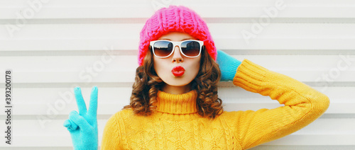 Winter portrait close up of young woman blowing red lips sending sweet air kiss Fototapeta