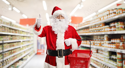 Santa claus in a supermarket carrying a shopping basket and gesturing thumbs up
