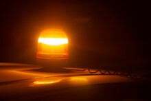 Closeup Of An Amber Strobe Warning Light On The Roof Of A Car At Night. Emergency Concept