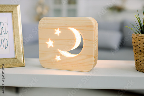 Close up cropped image of decorative wooden night lamp with moon and stars picture, on light table with flower pot and photo frame Fototapet