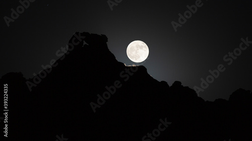 Tela The second full moon in October 2020 a blue moon rises over the ridge of a sandstone mountain near Zion National Park Utah