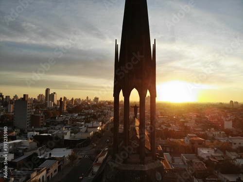 Fotografia Escultura del campanario de una de las iglesias de la ciudad con un fondo del señor Jesus extendiendo los brazos al sol en forma de gratitud