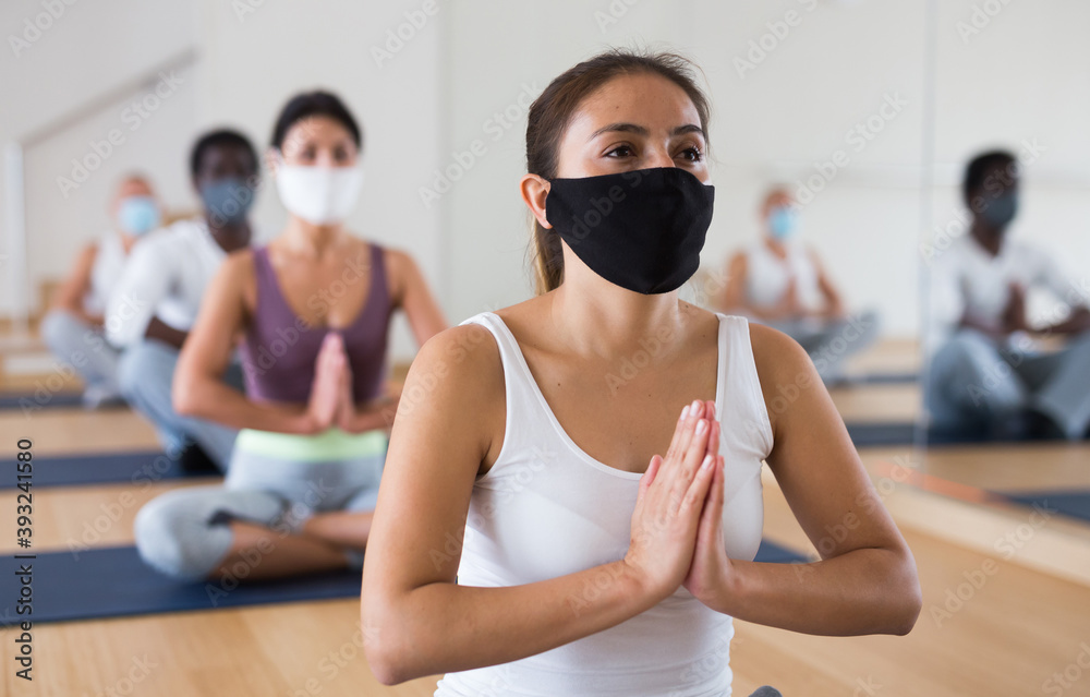 Fototapeta Young woman in face mask for viral protection sitting in lotus position practicing meditation at group yoga class