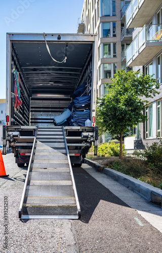 Fotografia Big rig semi truck with open box trailer stands on the street near an apartment