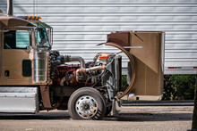 Brown Big Rig Semi Truck With Open Hood For Checking That The Engine Is Working Properly During A Stop In The Delivery Schedule