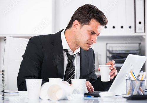 Tired man with loosened tie and disposable cup working in hot office Wallpaper Mural