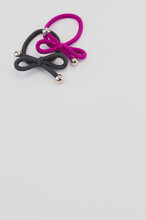 Vertical Shot Of Colored Hair Bands With Silver Beads On A White Background With Space For Your Text