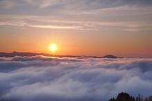 雲海と太陽。大地を覆う雲と壮大な空の風景。