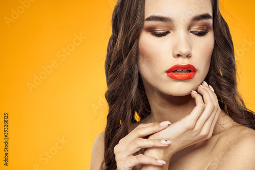 Foto beautiful brunette red lips bare shoulders skin care yellow background