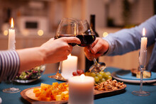 Lovers Clink Wine Glasses In Dining Room For Relationship Anniversary. Happy Cheerful Young Couple Dining Together In The Cozy Kitchen, Enjoying The Meal, Celebrating Anniversary Romantic Toast