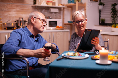 Obraz Elderly woman browsing on tablet pc and disabled husband in wheelchair holding wine glass. Imobilized handicapped senior husband browsing on phone enjoying the festive male, drinking a glass of red - fototapety do salonu