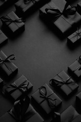 Panel Szklany Boks Arranged Gifts boxes wrapped in black paper with black ribbon on black background. Christmas concept