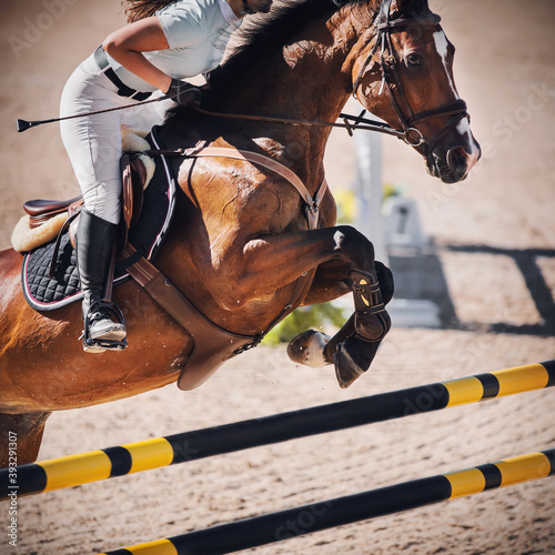 A beautiful Bay sports horse with a rider in the saddle jumps over a high yellow and black barrier in an outdoor arena. Equestrian sport. Horseback riding.