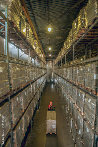 Warehouse worker going among the shelves in a warehouse