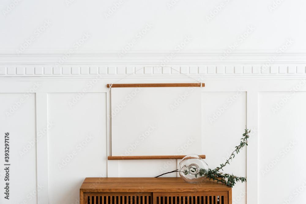 Fototapeta Blank frame hanging above a wooden cabinet