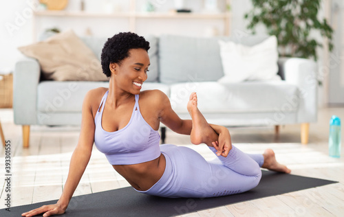 Obraz Sporty African American woman stretching her leg on yoga mat at home - fototapety do salonu