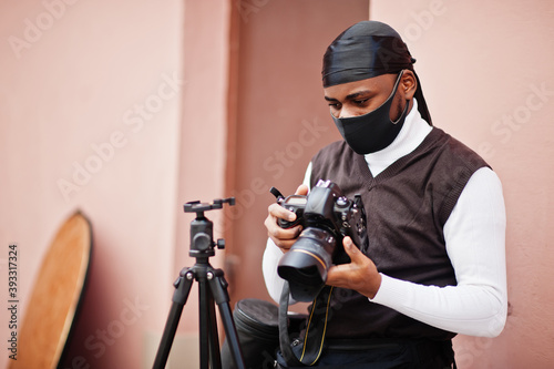 Young professional african american videographer holding professional camera with pro equipment. Afro cameraman wearing black duraq and face protect mask, making a videos. - fototapety na wymiar