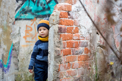 Foto Child, posing in an old ruin building, sprayed with graffiti