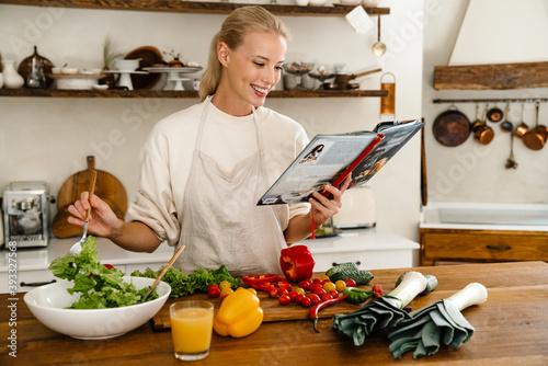 Tela Beautiful joyful woman reading cookbook and smiling while making lunch