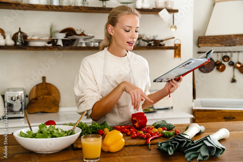 Foto Beautiful thinking woman reading cookbook while making lunch