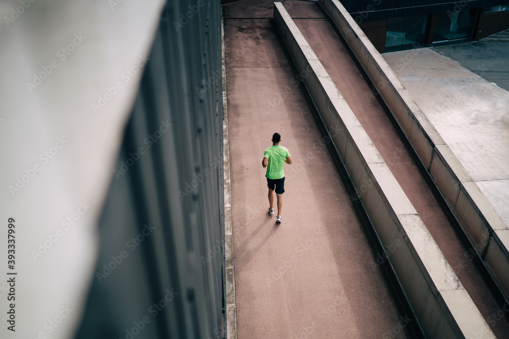 Fototapeta Back top view of strength triathlete dressed in sportswear spending workout time for sprinting and speed running, unrecognizable male jogger doing cardio training for prepare to marathon race
