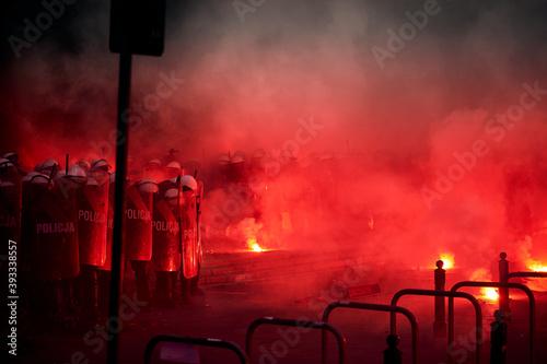 Fototapeta Police cordon and red flares during street protest obraz