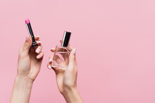 Cropped View Of Woman Holding Lipstick And Bottle With Perfume Isolated On Pink