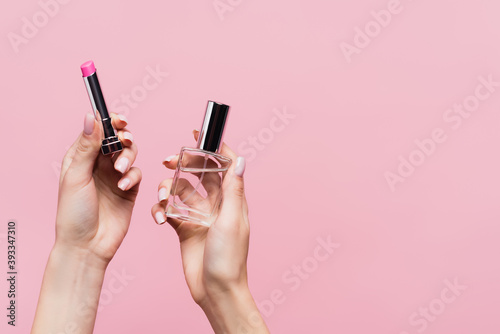 Fototapeta cropped view of woman holding lipstick and bottle with perfume isolated on pink obraz