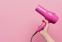 Cropped View Of Woman Holding Hair Dryer Isolated On Pink