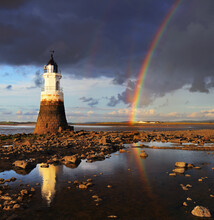 Plover Scar Lighthouse Built In 1847 Glistens In The Setting Sun Whilst The Last Of The Day's Hail Showers Clear Out To Sea At Cockersand Abbey Near Lancaster.