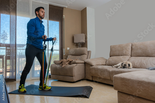 Carta da parati Latin man, doing a workout in his living room with a rubber band