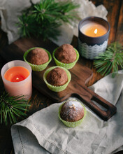 Rum Balls With Powdered Sugar On A Wooden Cutting Board, Next To Candles And Pine Twigs On A Wooden Table