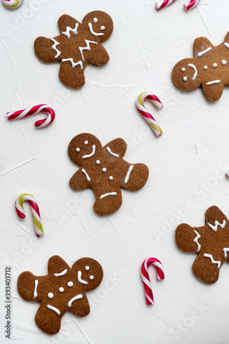 Fototapeta Christmas candy cans and gingerbreads man cookies on white background obraz