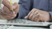Older Man With Yellow Pen In Wrinkled Hand Writing Letters In Croosword Or Sudoku During Coronavirus Quarantine